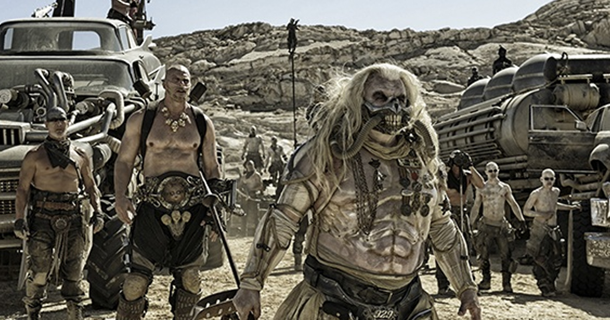 Shot of Immortan Joe standing in front of cars with his warboys and son