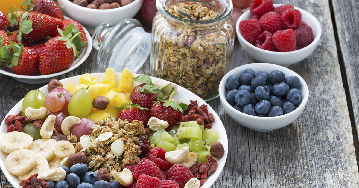Large array of bowls of fruit and granola on a old wooden table