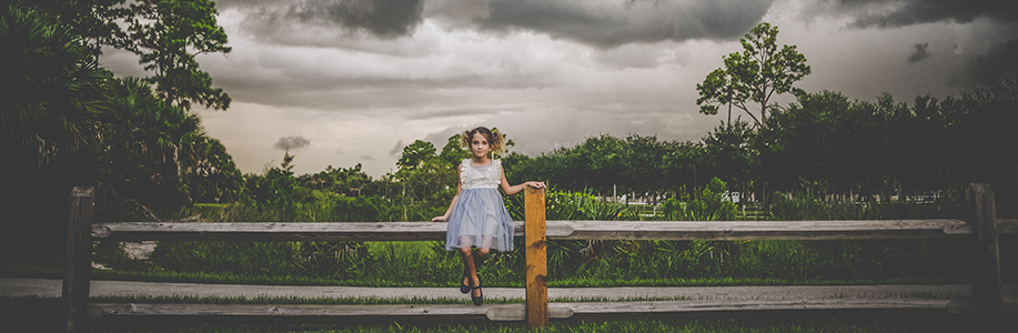 Young girl sitting on a fence with a dark storm front behind her