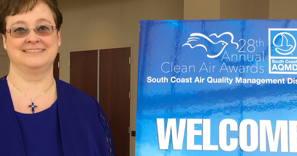 Volunteer in front of clean air sign