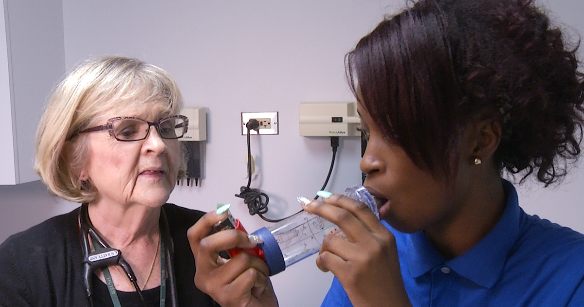 Nurse giving asthma MDI to youth
