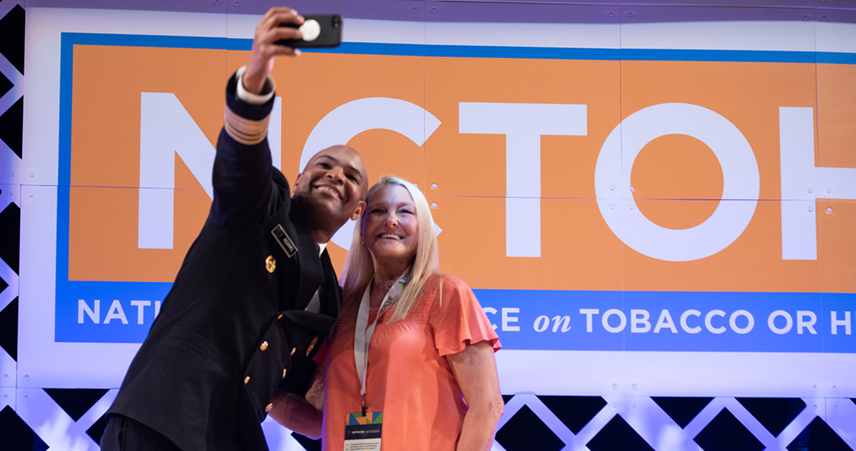 Two people taking a selfie in front of the NCTOH logo