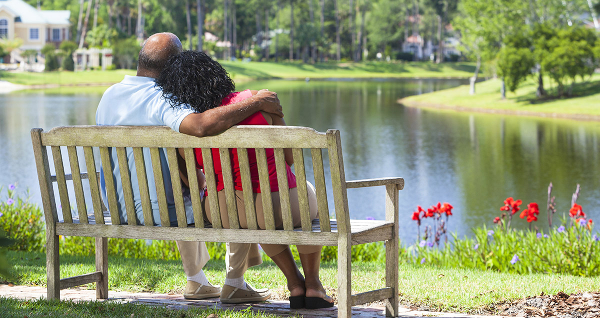 Man and woman sitting on a bench overlooking pond