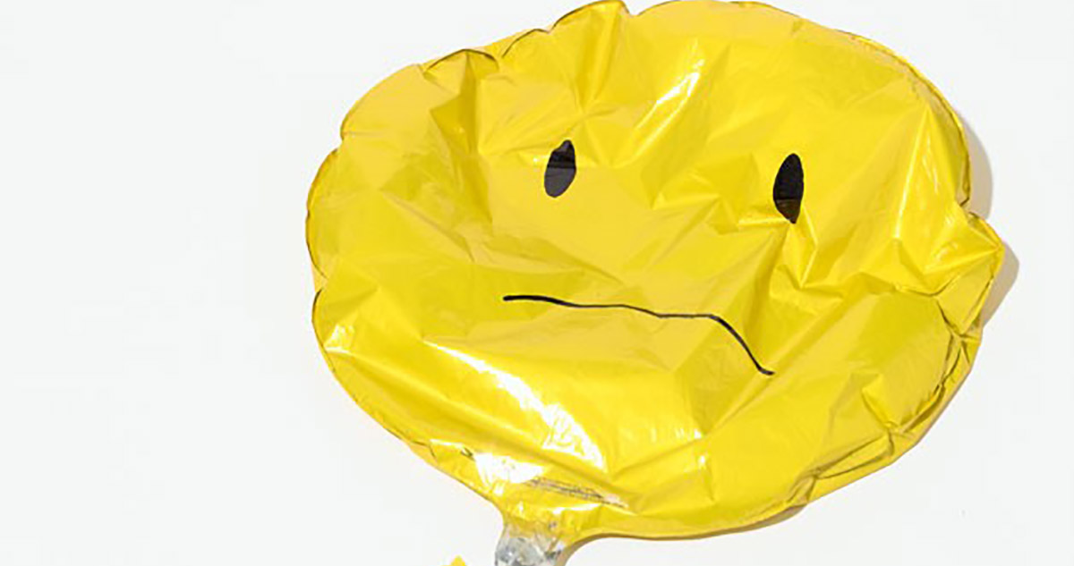 deflated frown face balloon