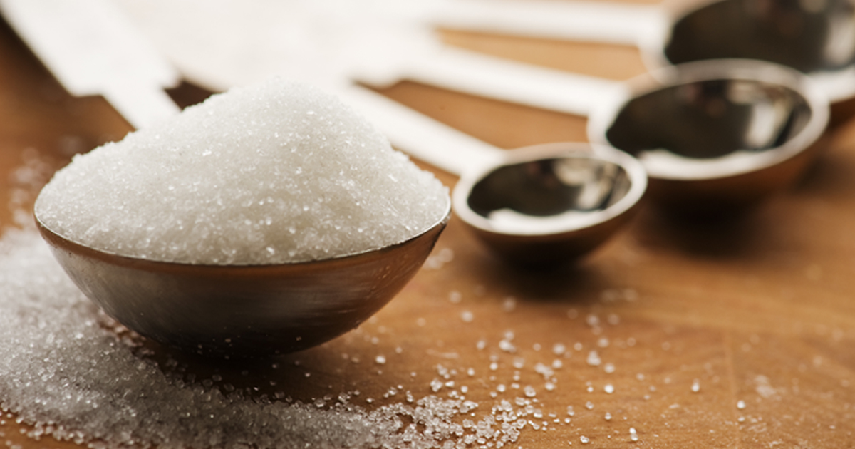 Measuring spoons of sugar on table