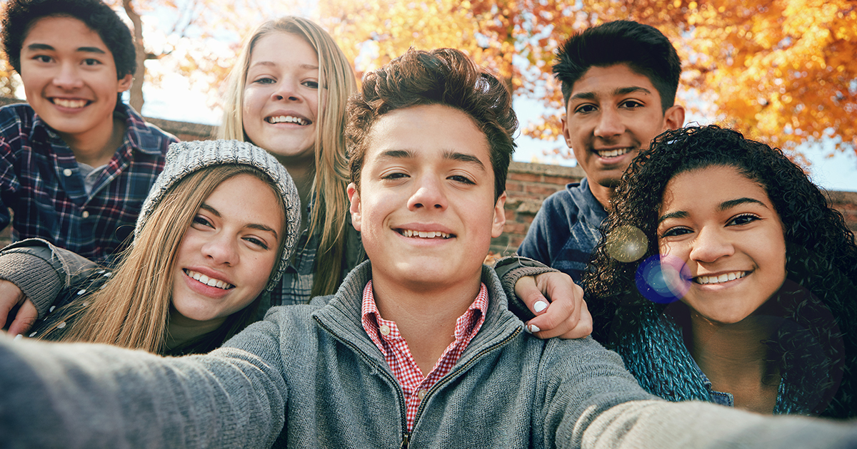 Group of teenage kids with fall background.