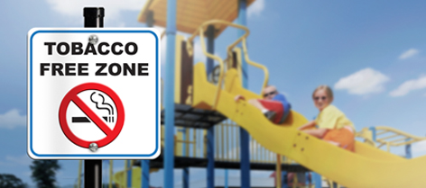 Tobacco free zone sign in front of children's playground